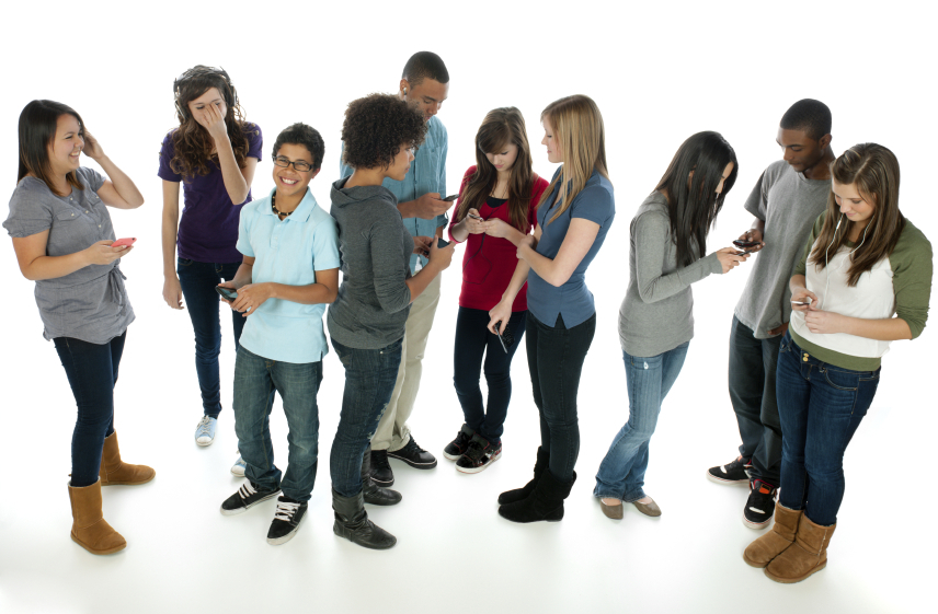 A large, diverse group of teens using various electronic devices.
